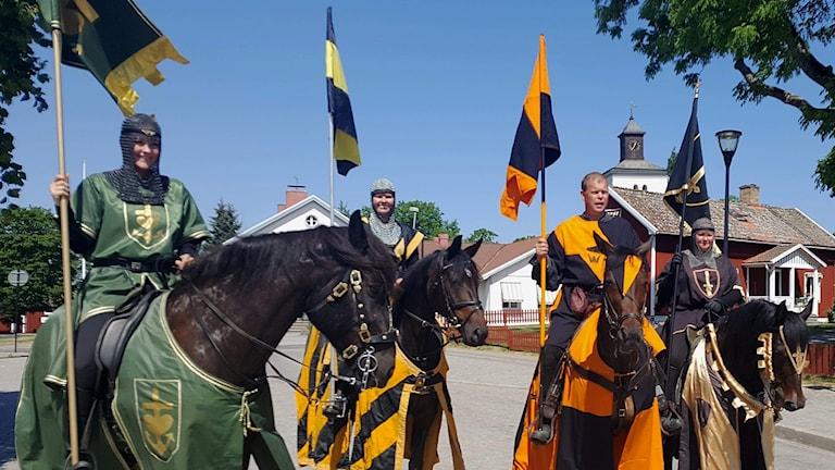 Fyra riddare på häst som håller i flaggor.