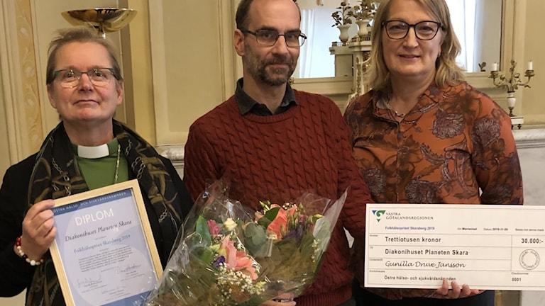 Tre personer som håller i ett diplom och en blombukett samt en prischeck.