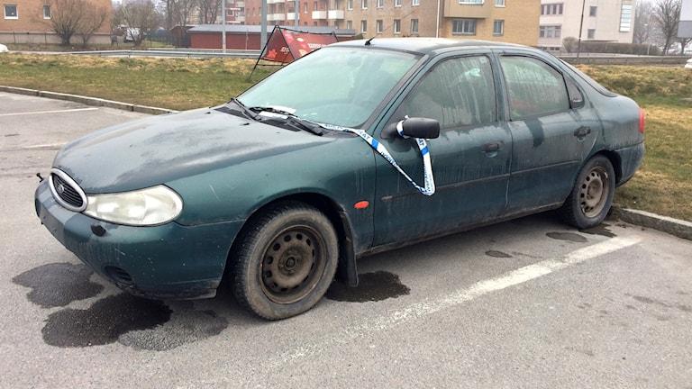 Grön skrotbil på en parkering