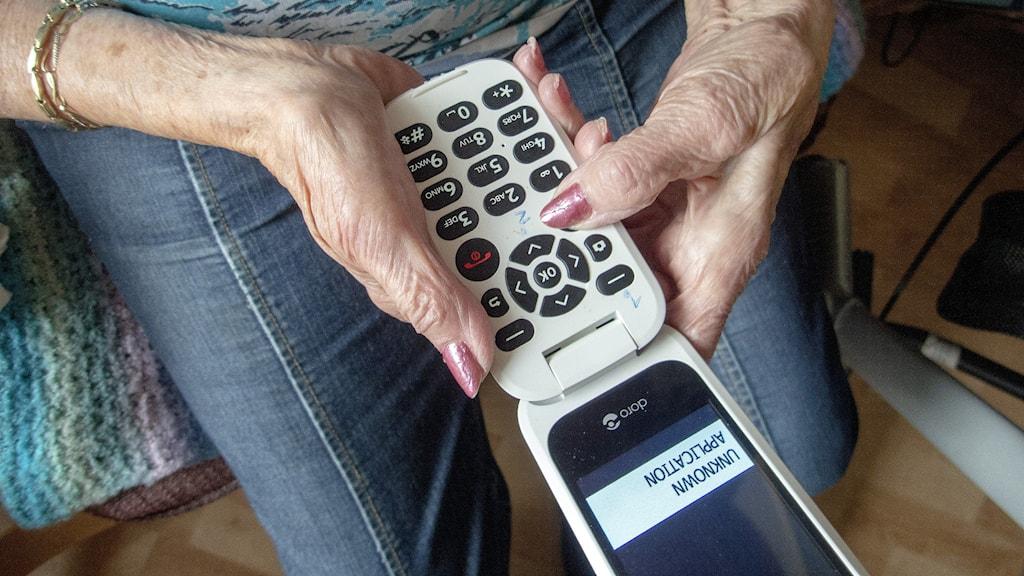 En äldre kvinna sitter med en vikbar mobiltelefon i händerna.