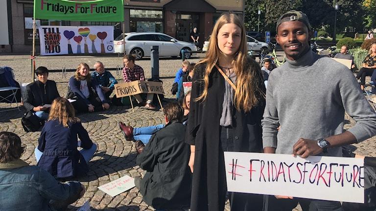 Två personer håller i en skylt och strejkar för klimatet.