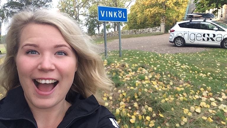 Emmy Rydstrand framför en Vinköl-skylt