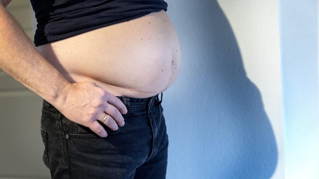 En överviktig man med putande mage.
