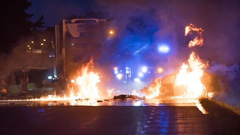 Bil som brinner, brinnande bensin på vägbanan, rök, blåljus och personal.