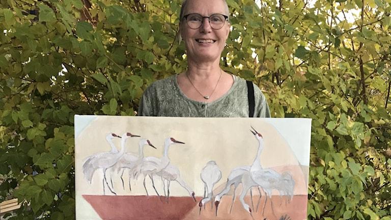 En kvinna håller i en akvarell med tranor på.