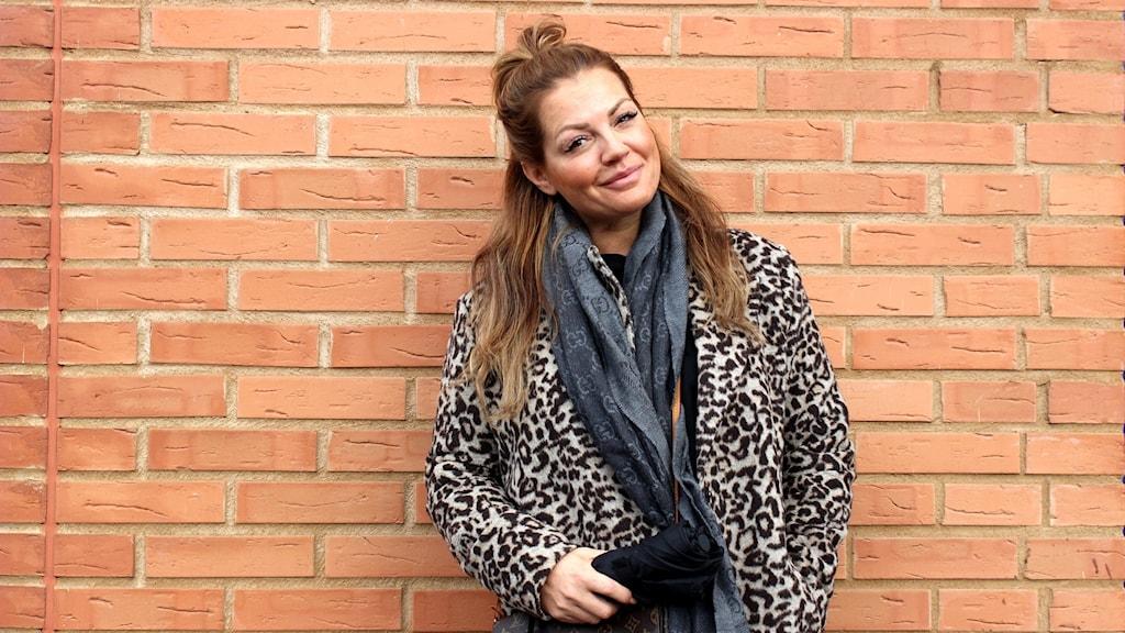 Halvkroppsbild på Johanna Toftby iförd en leopardmönstrad jacka framför en röd tegelvägg.