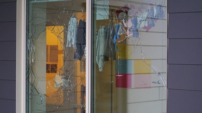 Krossad fönsterruta. Barnkläder på streck hänger innanför.
