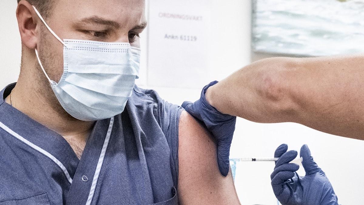 En vårdanställd vaccineras med en spruta.