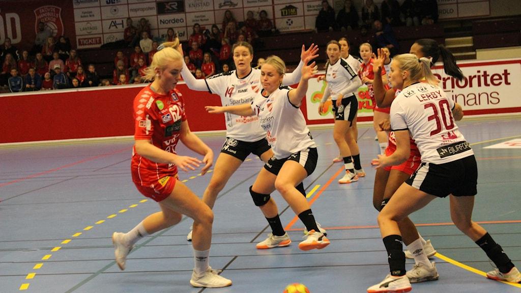 Flera kvinnliga handbollsspelare spelar på en plan.