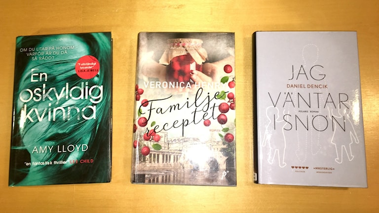 Tre böcker i en rad på ett bord.