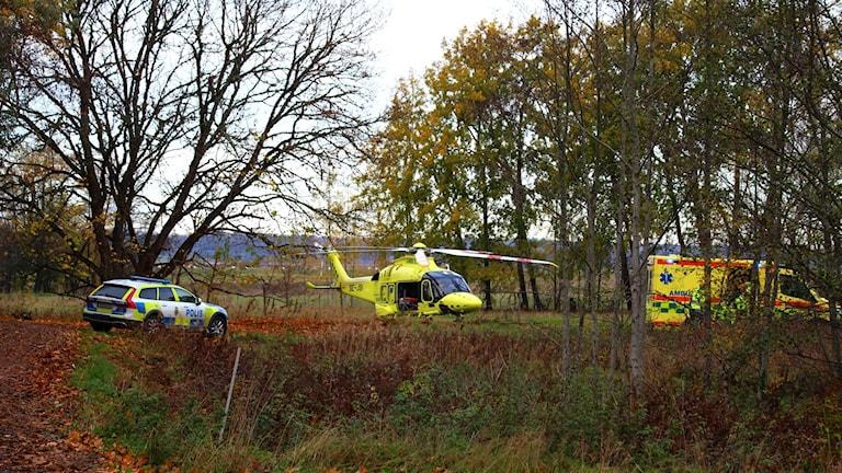 En polisbil en helikopter och en ambulans som står i en dunge.