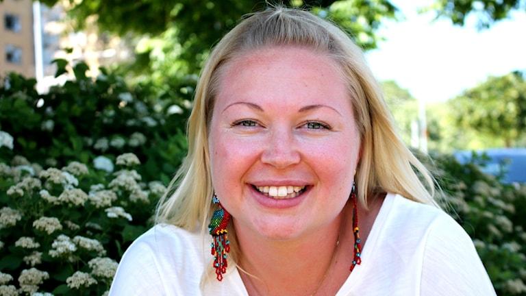 Blond kvinna i vit tröja som tittar in i kameran och ler