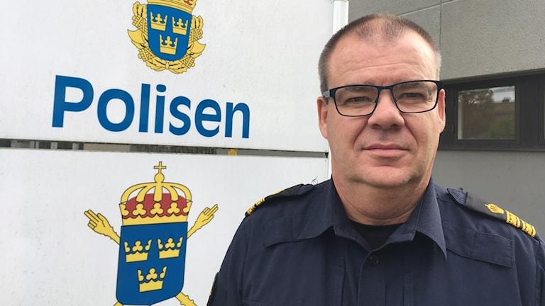 Porträttbild av Morgan Tärning framför skylt där det står polisen tillsammans med polisens logotype.