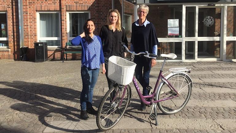 Loreen Hadad, Karin Lövgren och Margareta Kraepelien Lundh med en cykel framför biblioteket i Skara.