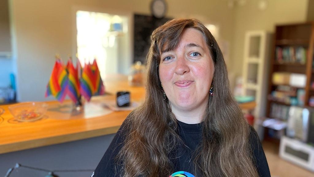 Désirée Sandström står i en lokal prydd med pride-flaggor på ett bord. Désirée ler och tittar in i kameran.