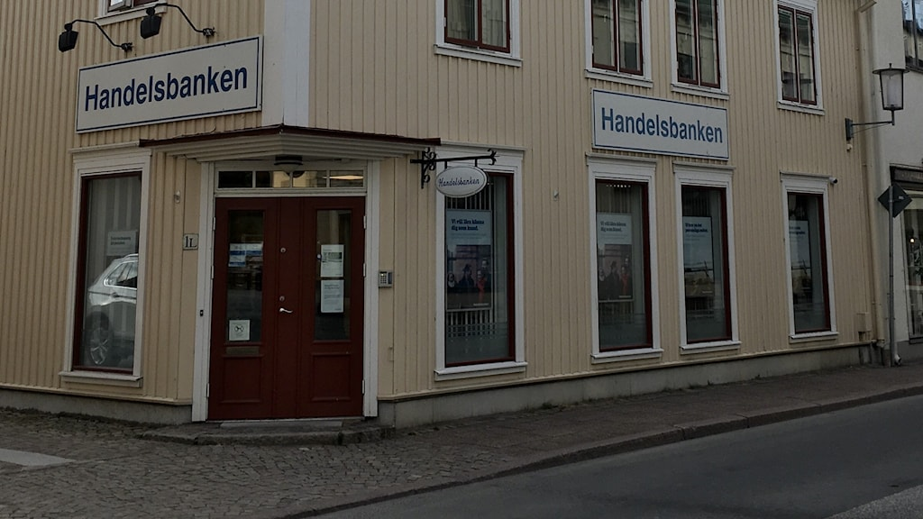 Handelsbankens kontor i Hjo sett utifrån. Det är ett trähus med gul fasad och skyltar med ordet Handelsbanken.