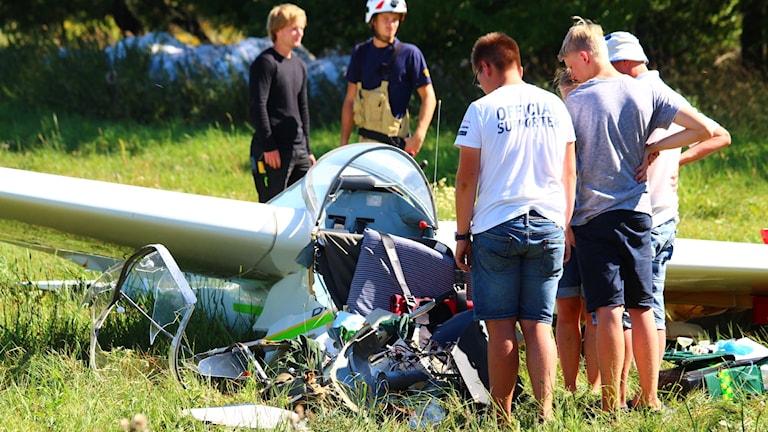 Tre personer ser ner på ett segelflygplan som landat våldsamt.
