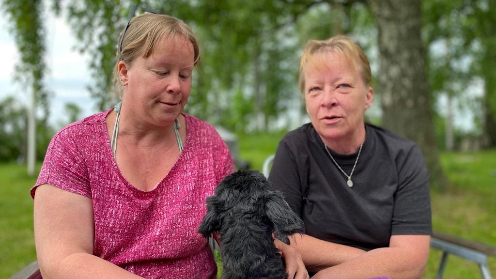 Syskonpar tillsammans med en hund i en trädgård i Tidaholm.