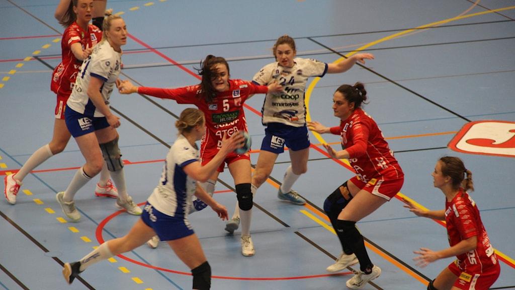 Flera kvinnliga handbollsspelare spelar på en blå plan.