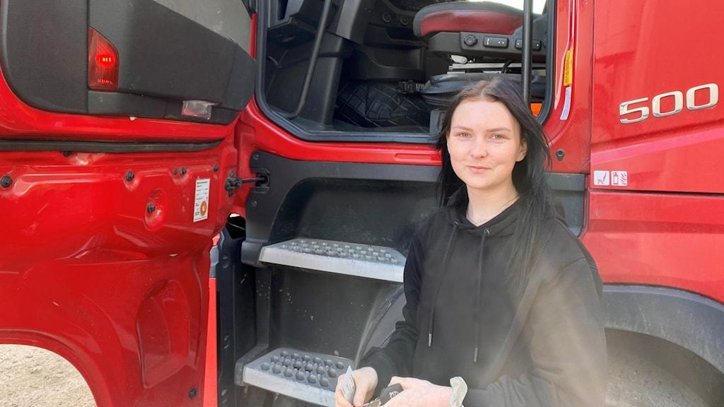 Micaela står framför hytten till en röd lastbil. Hon tittar in i kameran och ler lite.