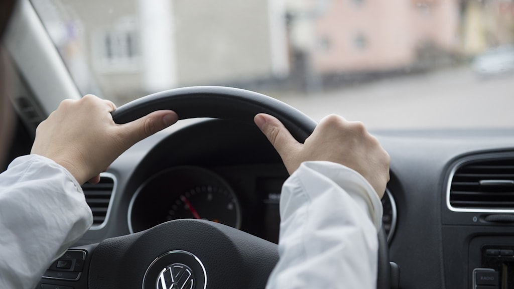Två händer på en bilratt.
