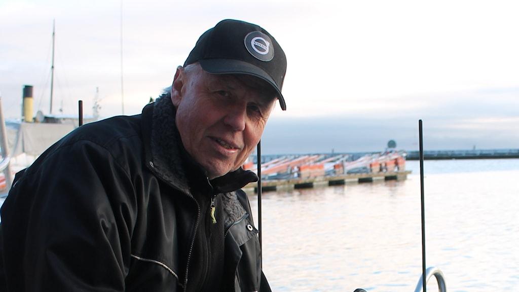 Yrkesfiskaren Enar Ahlin står med fiskenät i handen på sin båt i Hjo hamn.