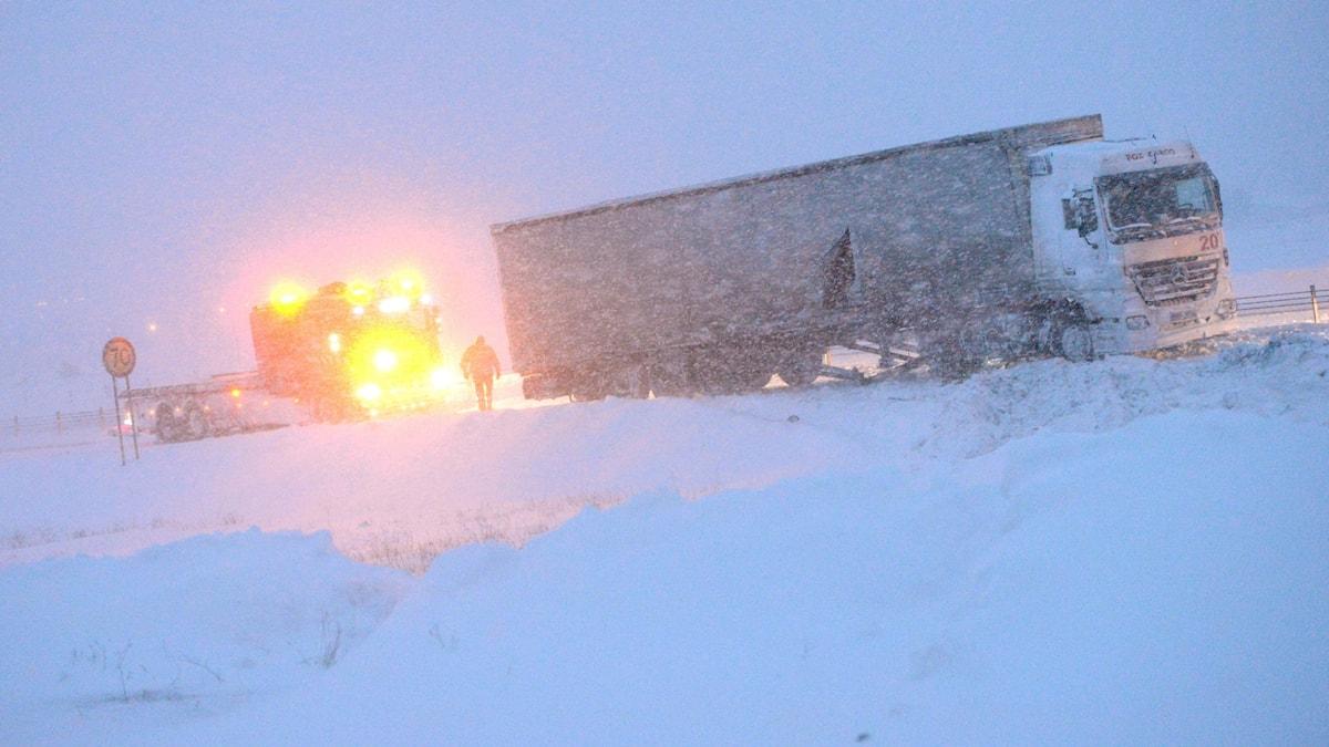 En lastbil står stilla på en väg medan snön yr och ett utryckningsfordon står med varselljusen tända bakom.