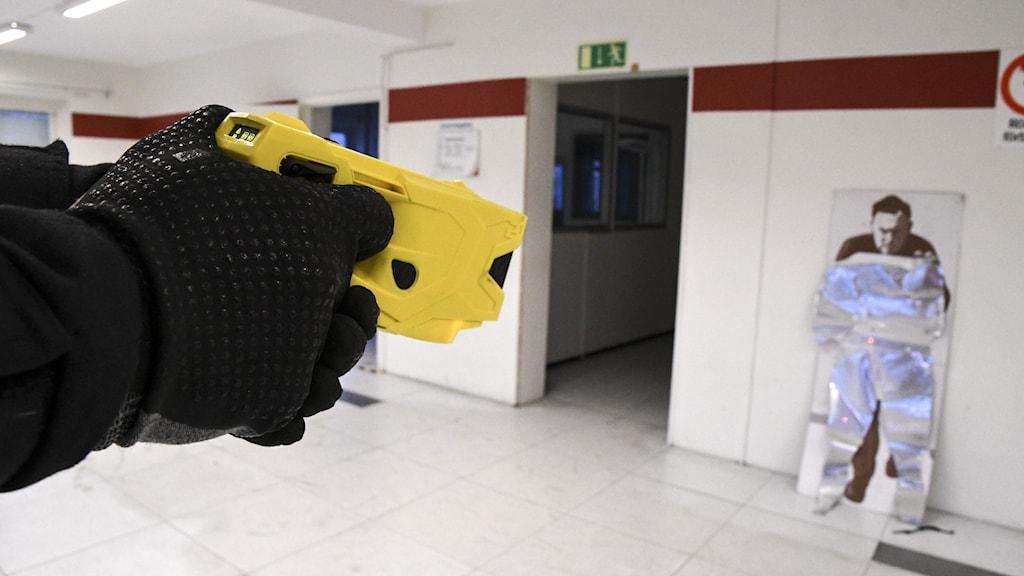 polisen använder ett elchockvapen mot en låtsasperson på papp.