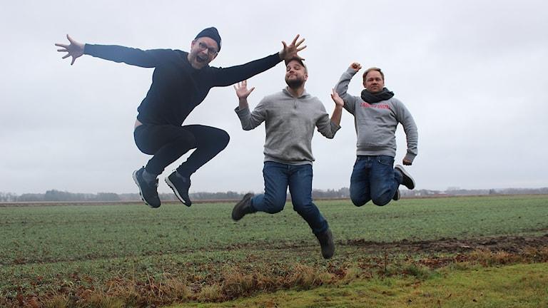 SKådespelarna Mårten Andersson och Victor Wigardt hoppar i luften på Varaslätten tillsammans med regissören Joakim Rindå.
