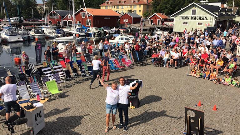 Ewa och Philip står i hamnen med solstolar bakom.