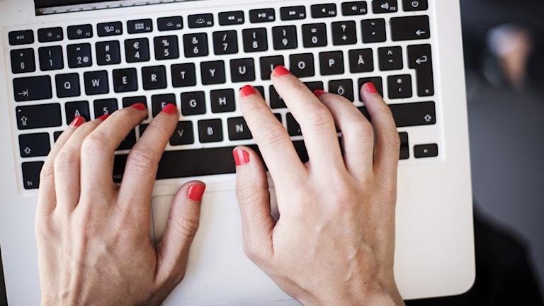 Ett par kvinnliga händer skriver på ett tangentbord.