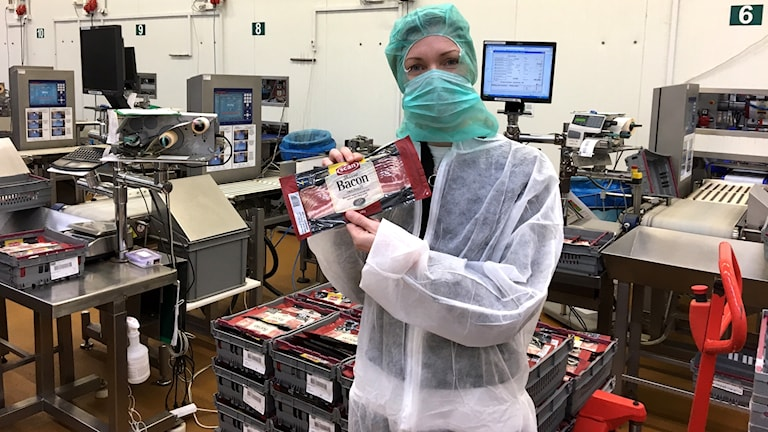 Linnéa Frimodig som håller i ett paket bacon i en fabrik.