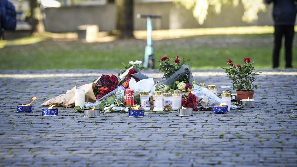 Tända ljus och blommor i närheten av platsen där artisten Einár sköts till döds i Hammarby sjöstad på torsdagskvällen.