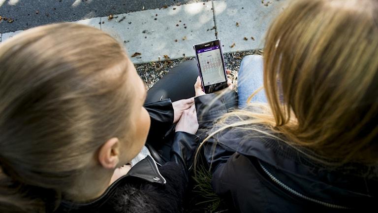 Två unga kvinnor tittar på p-appen Natural Cycles.