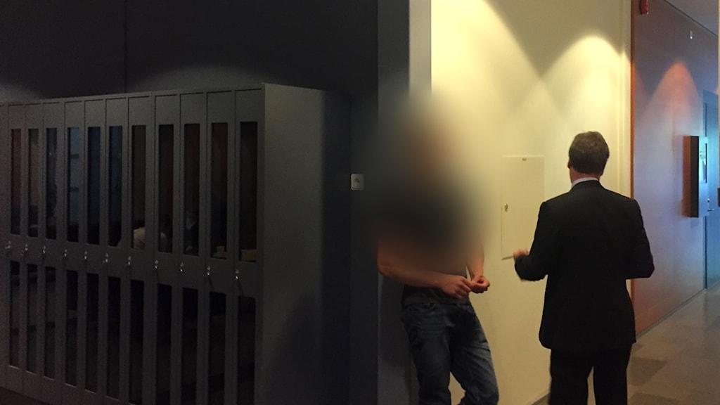 En man står i en korridor med sin advokat. Mannen är pixlad.