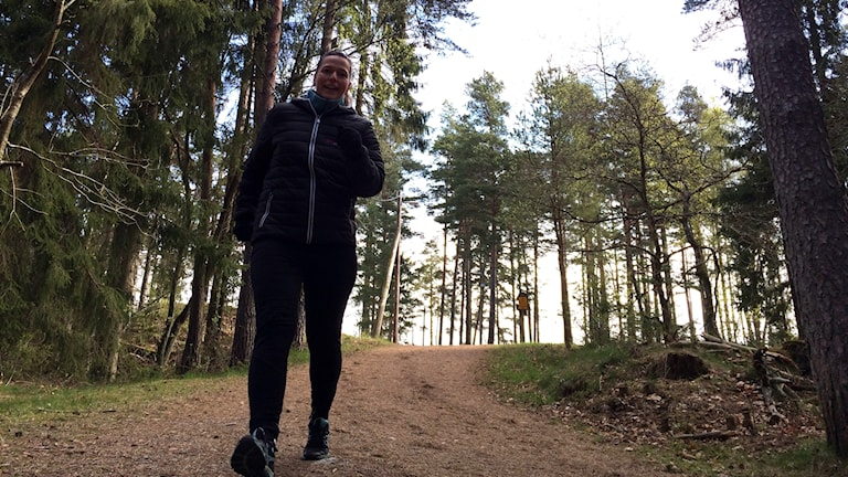 Katarina Roos springer i mot kameran i en skog