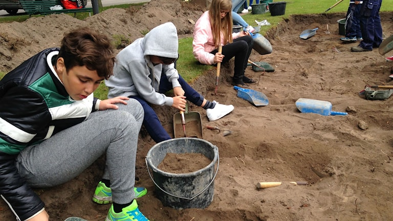 Wennerbergsskolans elever jobbar i utgrävningen i Lidköping. De sitter i en ungefär halvmeter djup rektangel och använder spadar och hinkar för att få upp jord.