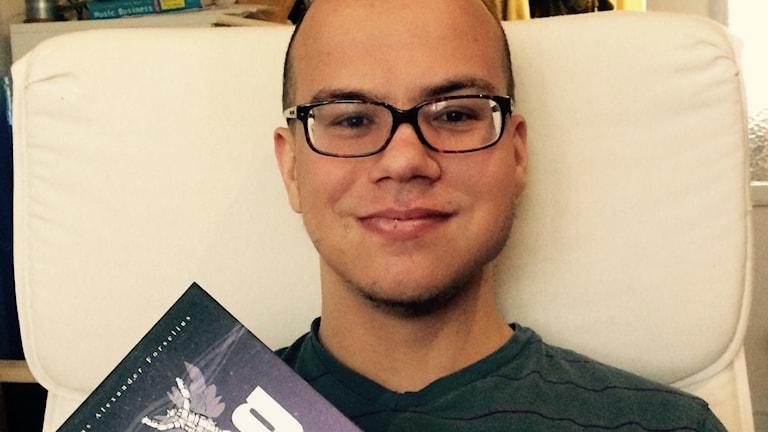 Alexander Forselius med sin bok om hur det är att leva med autism och ADHD.