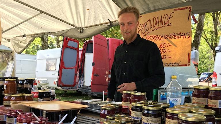 En ung man står i ett marknadsstånd och säljer sylt.
