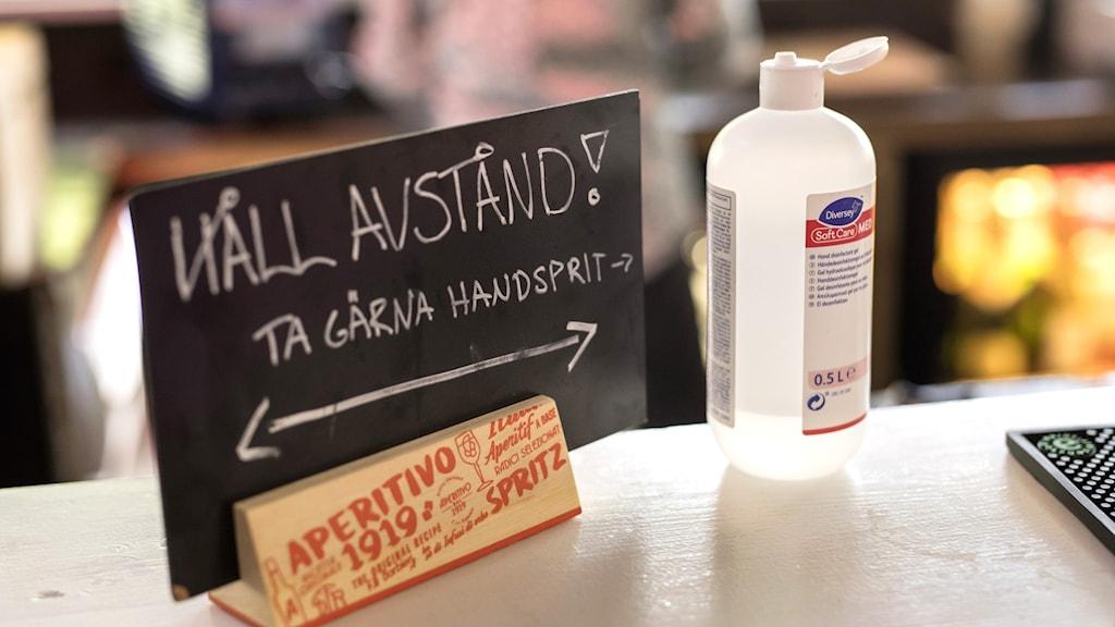 En skylt står på en bänk med texten Håll avstånd. Bredvid står en flaska handsprit.