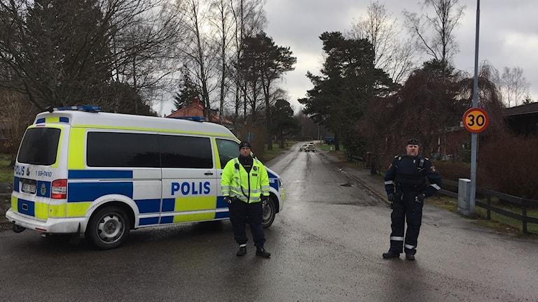Polisen står nära det avspärrade kvarteret.