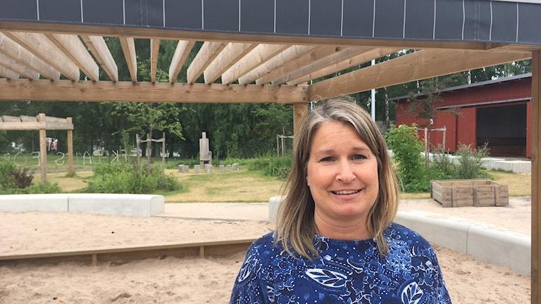 Elin Lundqvist framför ett solskydd med markis på förskolans gård.