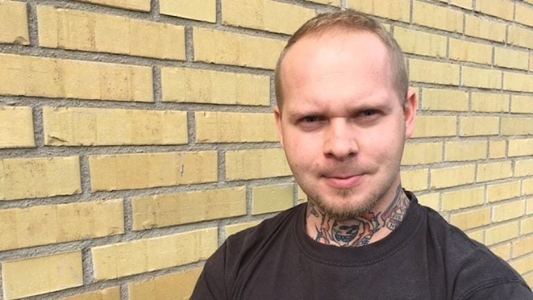 Porträttbild av Tommy Magnusson framför en gul tegelvägg.