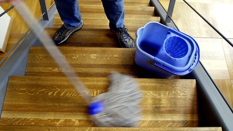 Person svabbar en trappa med en golvmopp.