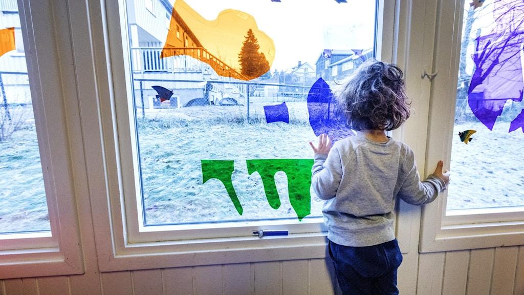 Ett litet barn tittar ut genom ett fönster som är målat.