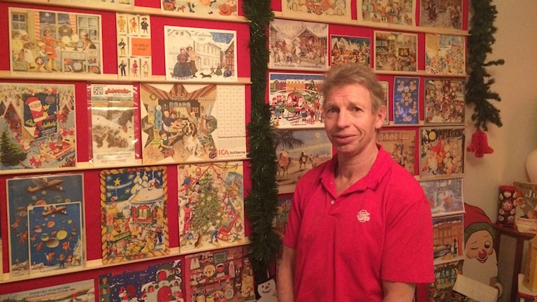 Ronny Hansson i Skövde står framför den stora väggen med olika julkalendrar uppsatta.
