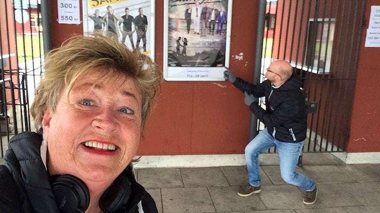 Ewa tittar in i kameran och Christopher pekar på en affisch.