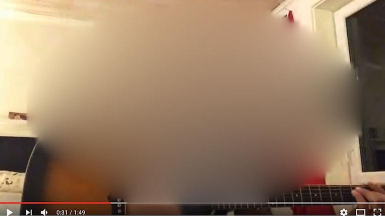 Skärmdump från filmklipp på nätet där ledaren för Soldiers of Odin sjunger en sång med rasistiskt och nazistiskt budskap. Personen på bilden har