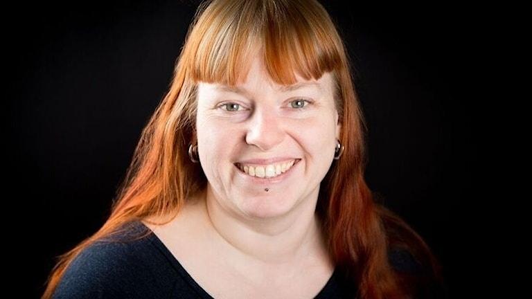 Åsa Roos är på bilden. Hon har rätt hår, gröna ögon och är framför en svart bakgrund.