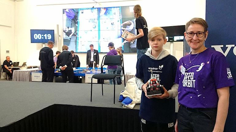 En pojke och en kvinna står framför en robottävling.